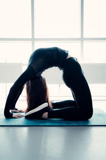 Full length of woman exercising on floor against window
