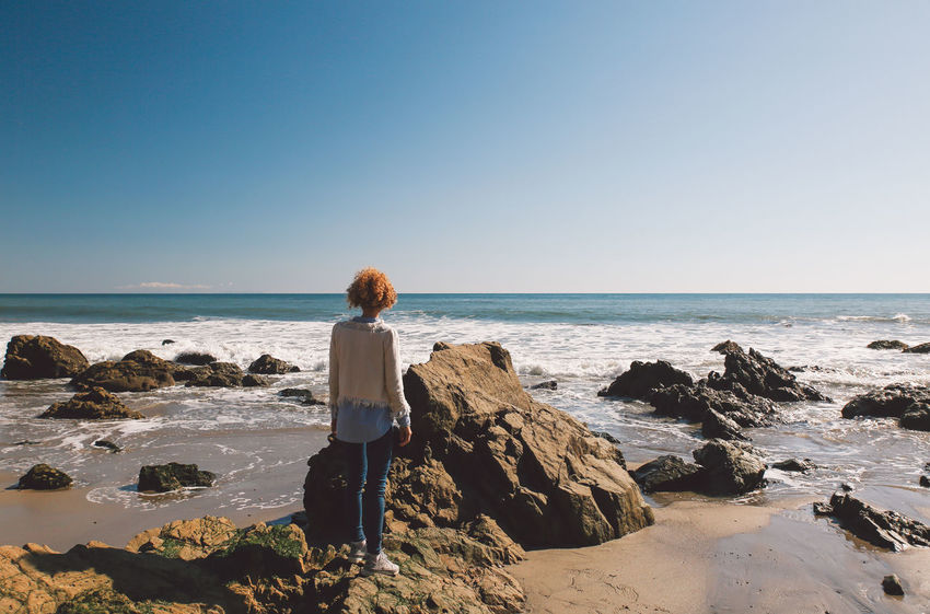 California El Matador Beach Beach Beauty In Nature Blue Clear Sky Curly Hair Day Full Length Girl Horizon Over Water Leisure Activity Lifestyles Looking At View Nature One Person Outdoors Real People Rear View Rock - Object Scenics Sea Sky Standing Sunlight Tranquil Scene Tranquility Water Women