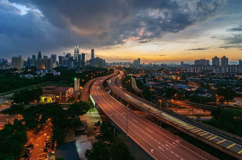 Dramatic scenery of Kuala Lumpur city skyline during sunset Architecture Buildings Built Structure City City Life City Street Cityscape Cloud - Sky Cloudy Diminishing Perspective Dramatic Sky Illuminated Orange Color Outdoors Road Scenic View Sky Skyscrapers Sunset The Way Forward Today's Hot Look Travel Destinations Vanishing Point Mobility In Mega Cities