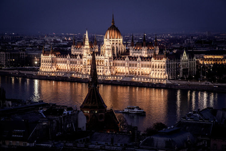 Hungarian Parliament Building By River In City At Night