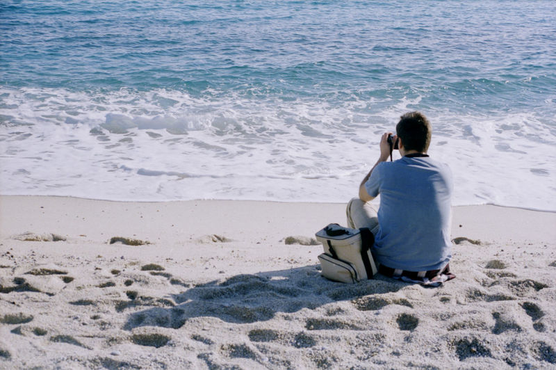 Rear view of man photographing while sitting at beach