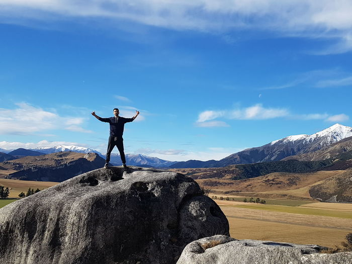 Man with arms outstretched standing on rock against cloudy sky
