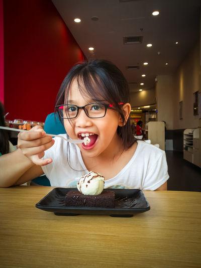 Girl eating dessert while sitting in restaurant