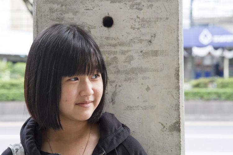 Portrait of smiling teenage girl looking away