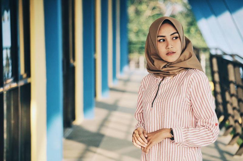 Woman wearing hijab while standing on corridor