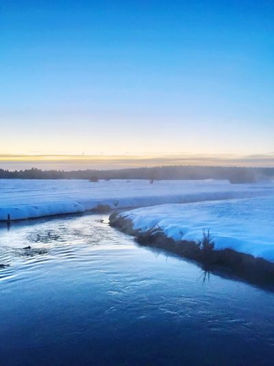 River Amidst Snow Covered Field Against Clear Sky