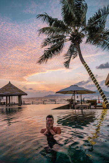 Man in infinity pool against sky at sunset