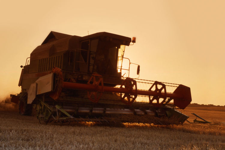harvester in ction in dramatic sunset light Harvest Season Harvester Orange Agricultural Machinery Agriculture Close-up Combine Combine Harvester Dramatic Light Farm Field Grass Harvesting Land Land Vehicle Landscape Machinery Mode Of Transportation Nature No People Outdoors Plant Rural Scene Sky Sunrise Sunset Transportation