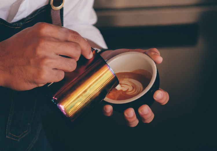 Midsection Of Barista Pouring Cream In Coffee At Cafe