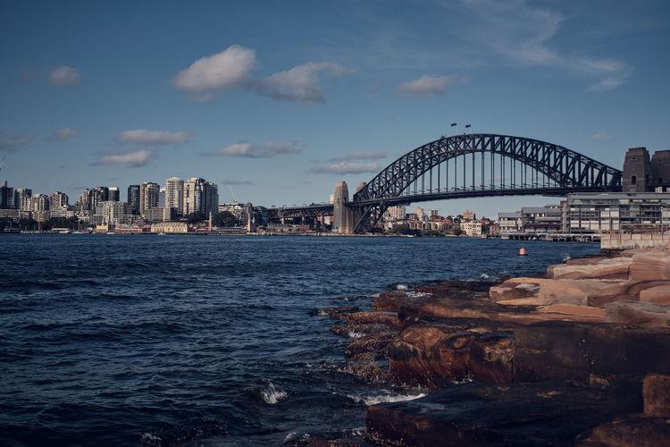 Arch bridge over sea against buildings in city