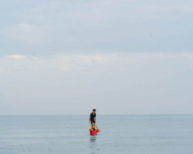 Father carrying son on shoulder in sea against sky