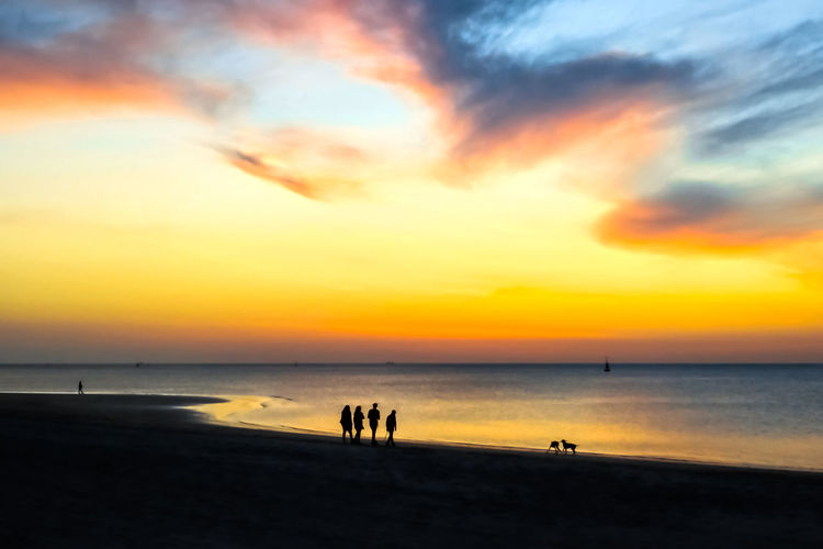 Silhouettes of people walking on the beach at sunset. Epic dramatic sunset. Beautiful orange, yellow and blue colors sunset sky for background. Sky Sunset Cloudscape Clouds Sunrise Background Cloud Beautiful Nature Sun Light Dramatic Summer Blue Sunlight Landscape View Heaven Orange Dawn Dusk Beauty Twilight Bright Color Weather Scene Red Horizon Cloudy Outdoor Day Scenic Morning Yellow Sunny Colorful Evening Atmosphere Sunshine Nobody Abstract Season  Sea Ocean Climate Space