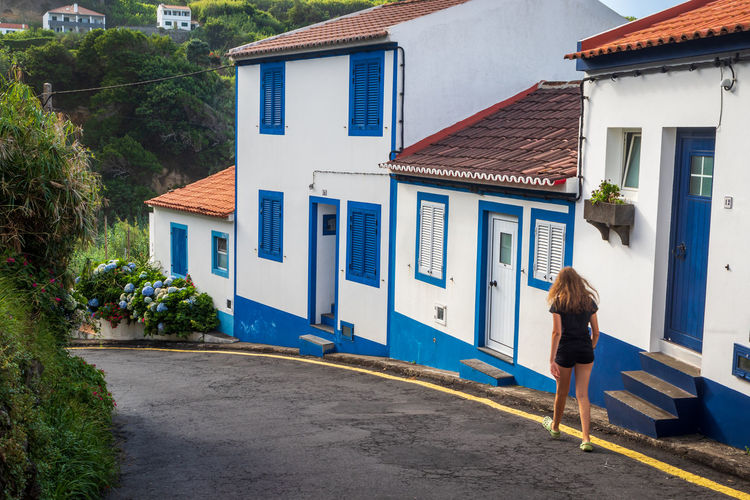 Back view of a teen girl walking down a steep street in los moinhos, porto formoso, azores