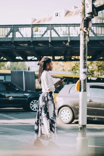 Side view of woman standing by car in city