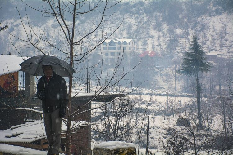 Man With Umbrella Betterlandscapes Travel Cool Weather Winter Human Condition Manali ,Himachal Pradesh Outdoors Snow Snowfall Peace Waiting Patience Inner Peace Tree Sky Day Water Mountain EyeEmNewHere The Portraitist - 2017 EyeEm Awards