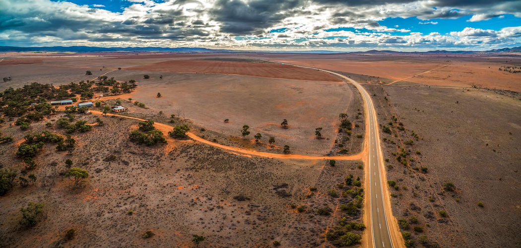 Rural highway bend in Australian outback under beautiful skies - aerial panorama Australia Australian Australian Landscape Outback Panorama Panoramic View Aerial Aerial View Arid Climate Beauty In Nature Climate Cloud - Sky Day Desert Environment Land Landscape Non-urban Scene Outback Australia Outdoors Remote Road Scenics - Nature Semi-arid