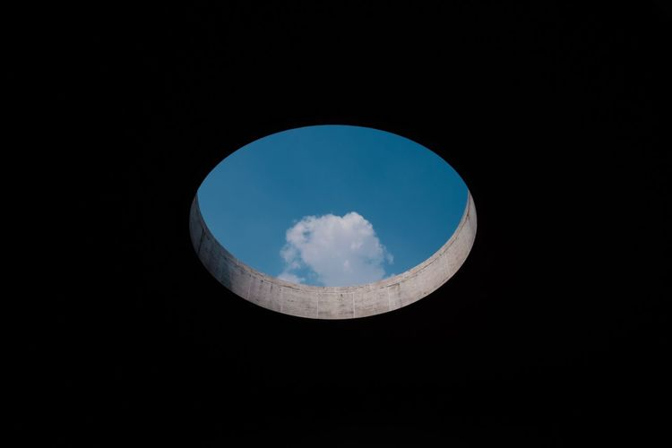 Low Angle View Of Blue Sky Seen Through Circular Hole