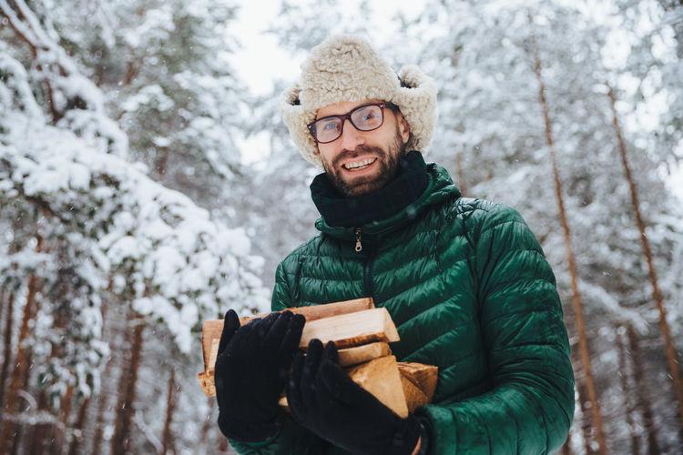 Portrait of man holding ice cream against trees