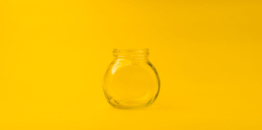Close-up of glass bottle against yellow background