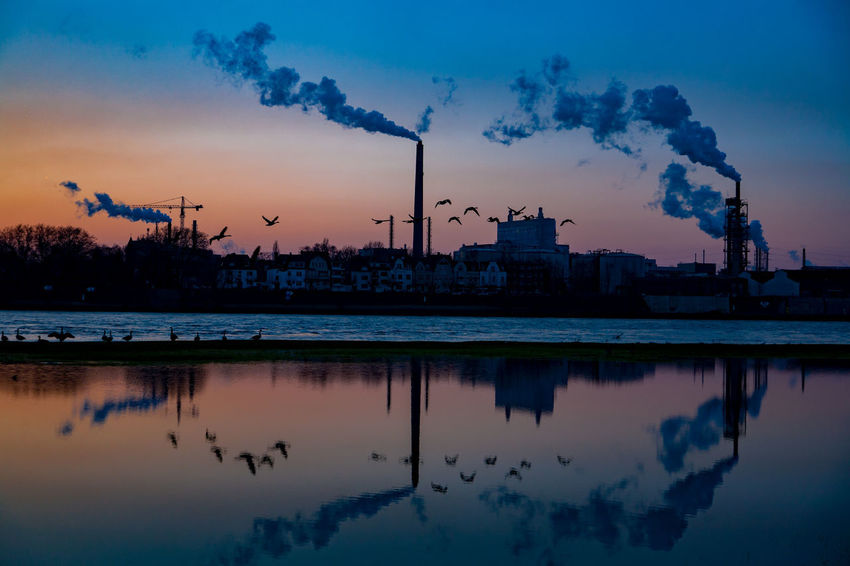 #meadows07 Rhein Ruhrgebiet Architecture Building Exterior Built Structure Chimney Day Emitting Factory Fumes Industry No People Outdoors Reflection Silhouette Sky Smoke - Physical Structure Smoke Stack Sunset Water Colour Your Horizn