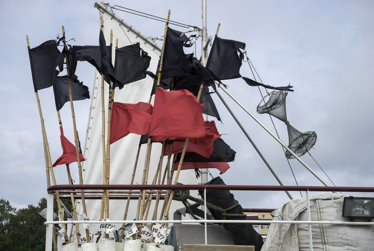Red and black flags on trawler against sky