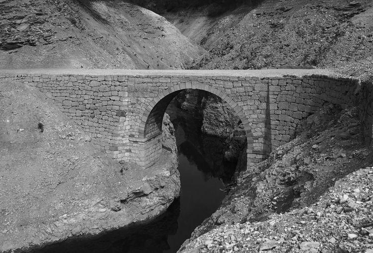 Bridge over stream against mountains
