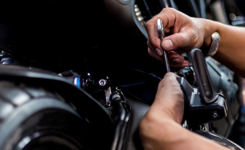 Cropped image of man repairing motorcycle at garage