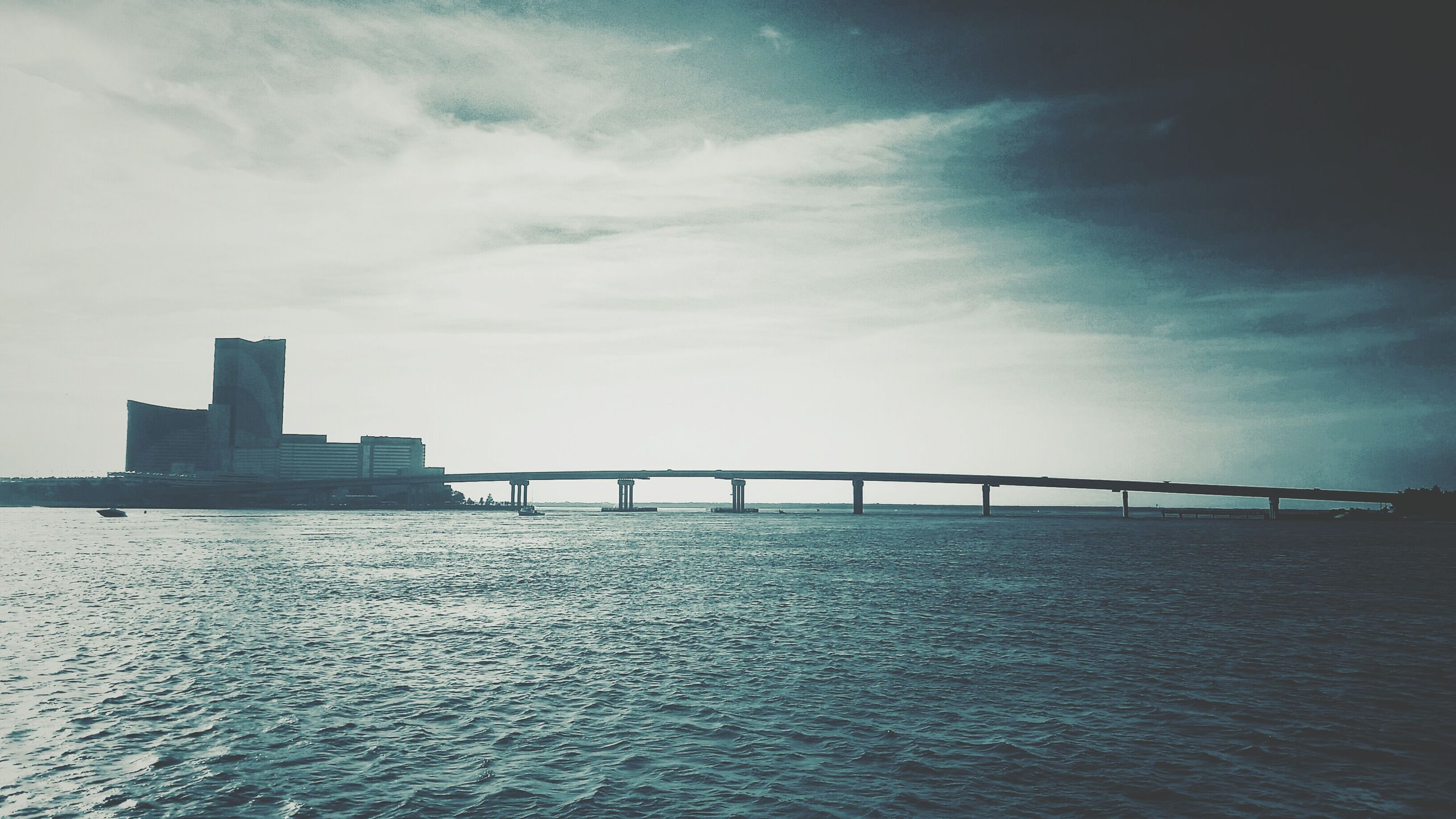 architecture, built structure, water, sky, waterfront, sea, connection, bridge - man made structure, building exterior, cloud - sky, river, rippled, bridge, cloud, nature, outdoors, city, tranquility, day, no people