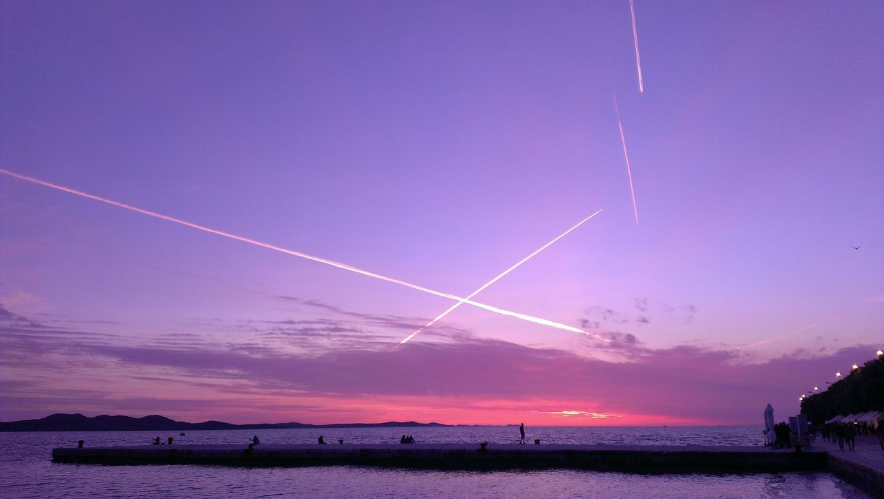 Scenic View Of Vapor Trails In Sky At Sunset