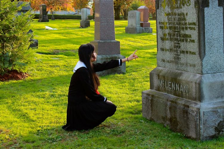 Young woman with headstone