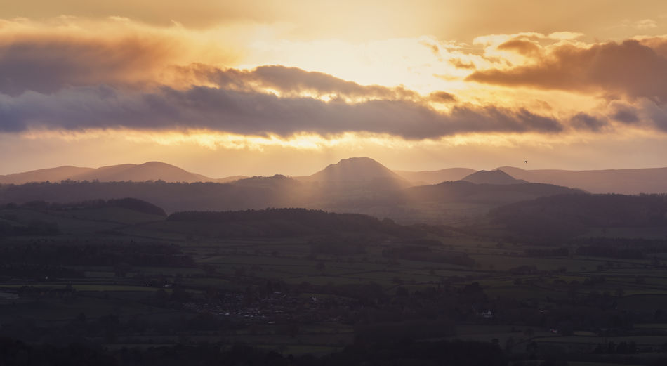 Sun beams through cloudy sky and hills at sunset over hilly countryside in UK Autumn Hills Aerial View Agriculture Beauty In Nature Day Eddiecloud Hills And Valleys Landscape Mountain Mountain Range Mountains Nature No People Outdoors Rural Scene Scenics Shropshire Sky Sun Sunlight Sunset Tranquil Scene Tranquility Tree