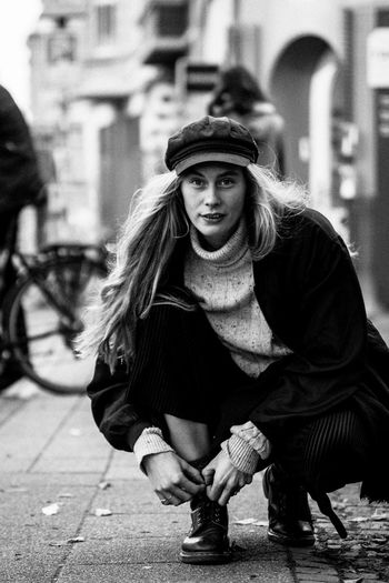 Portrait of woman tying shoelace on footpath
