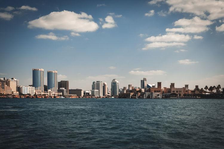 Sea by modern buildings in city against sky