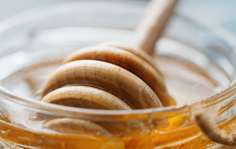 Close-up of honey dipper in jar