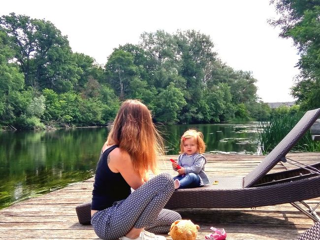 Mom and baby girl near the river Baby Girl Woman River Summer Family Tree Togetherness Sitting Water Women Childhood Bonding Relaxation Happiness Full Length Lakeside Tranquility Calm Tranquil Scene Idyllic Non-urban Scene Countryside Single Parent