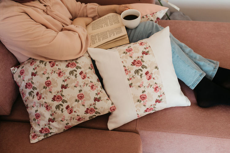 Low section of woman reading book sitting on sofa at home