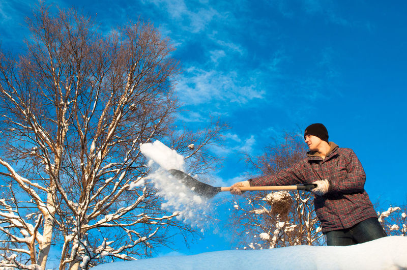 Low angle view of man shoveling snow against blue sky