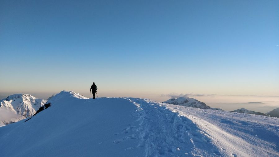 Man on snowcapped mountain against clear sky