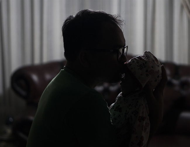 Side view of father kissing newborn daughter while sitting at home