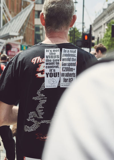 Rear view of man with text standing in city