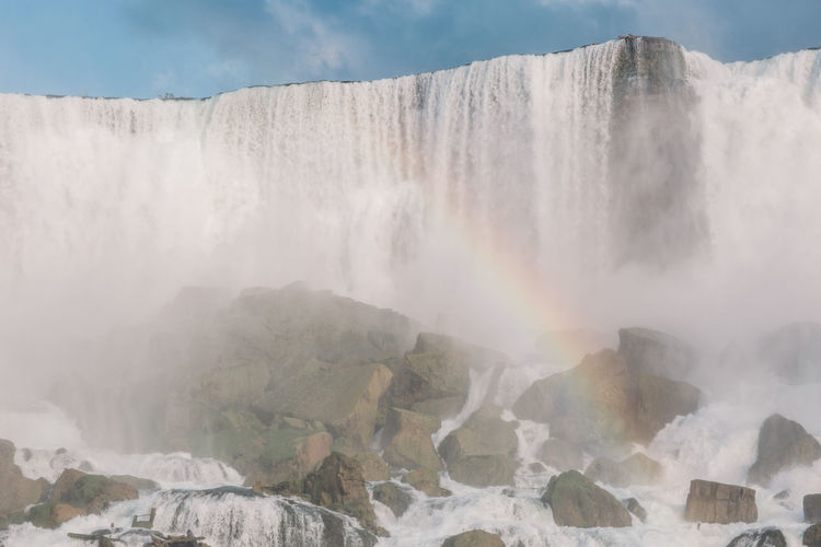 Scenic View Of Rainbow Against Waterfall