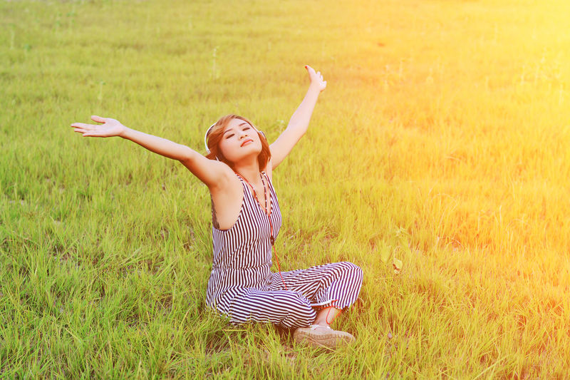 Arms Raised Casual Clothing Child Childhood Day Field Grass Green Color Happiness Human Arm Human Limb Innocence Land Leisure Activity Lifestyles Limb Nature One Person Outdoors Plant Real People Women