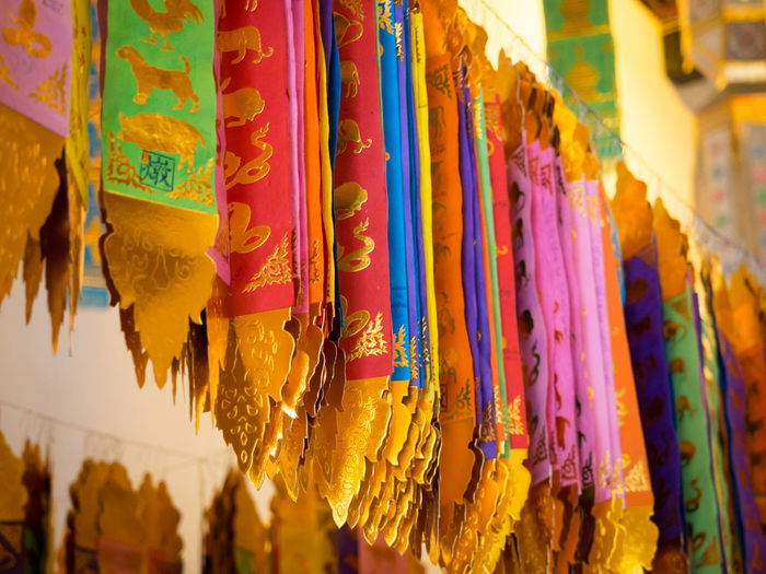 Close-up of multi colored flags hanging in buddhist temple wat chiang man, chiang mai, thailand