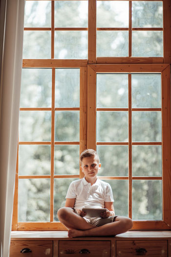 Full length of man sitting on table at window