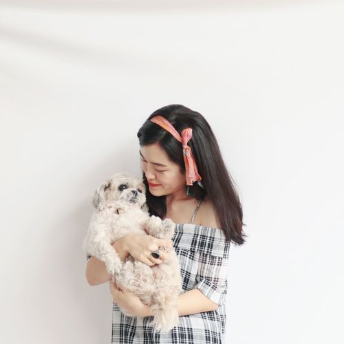 Young woman holding dog standing against white wall