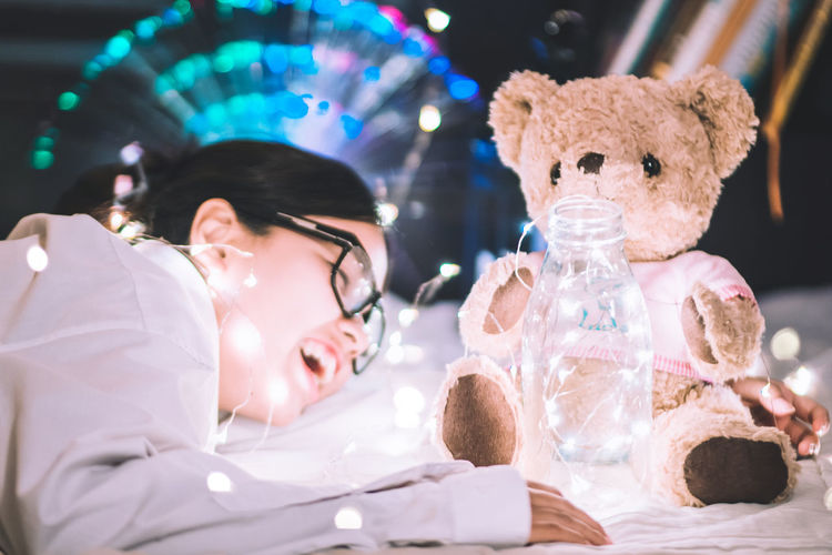 Close-up of girl with illuminated string light and teddy bear