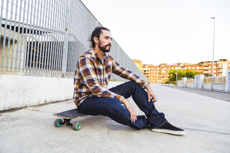 Young man sitting on skateboard in city