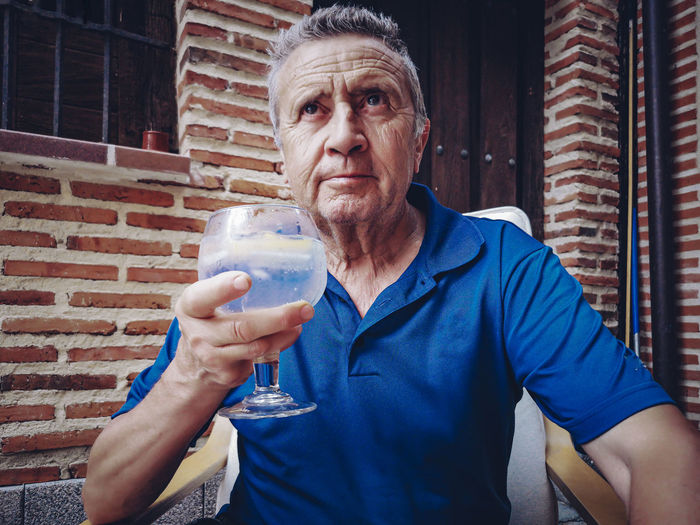 Portrait of mid adult man holding drink against wall