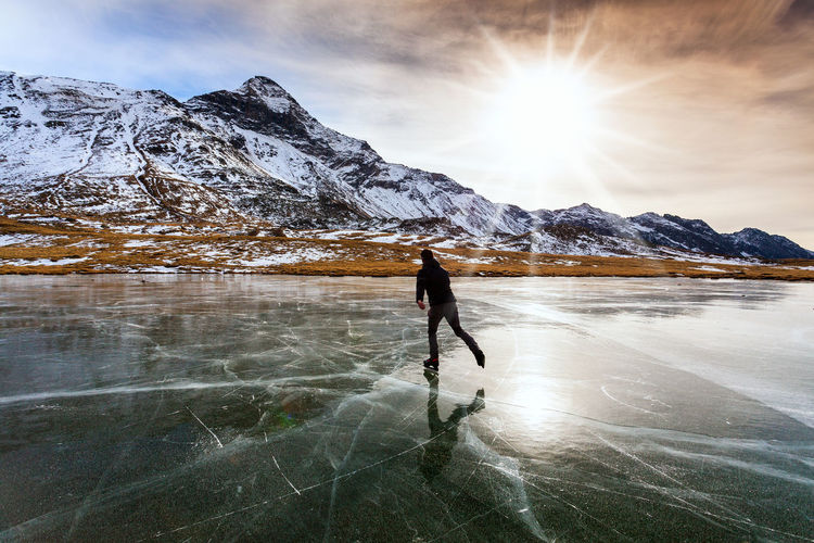 Woman walking on snowcapped mountain against sky during winter