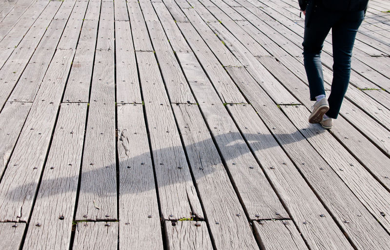 Young man and his shade walking on a wooden pier Boardwalk Body Part Casual Clothing Day Footpath Human Body Part Human Foot Human Leg Human Limb Jeans Leisure Activity Lifestyles Low Section Men One Person Outdoors Real People Rear View Shoe Standing Walking Wood Wood - Material